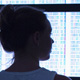 woman in silhouette looking at computer screens with genome data