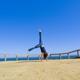 Woman doing handstand near ocean