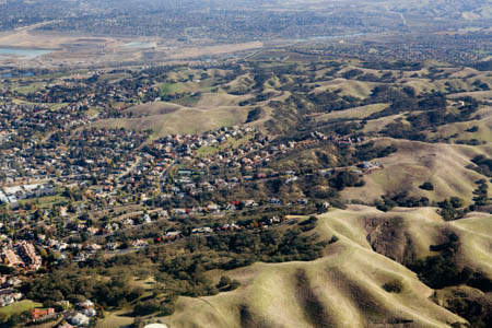 Aerial view of housing developments stretching out into rolling hills near the Santa Cruz mountains