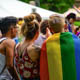 Young adults gathered outdoors at an event, some participants are wearing rainbow flags