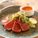 Seared tuna on a plate with dipping sauce