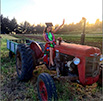 graduate sitting on a tractor at ucsc farm